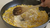cooks : Rice and corn vegetarian meal being stirred while cooking on stove