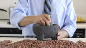 Man grinds raw cocoa beans with mortar and pestle