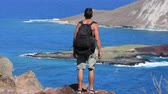 фитнес : Muscular shirtless Caucasian man hiking with backpack stops to sit and enjoy the view of arid islands in blue sea near Makapuu Beach in Oahu, Hawaii