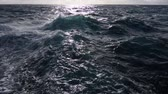 Rough ocean with turbulent surface waves while sun reflects on horizon after storm