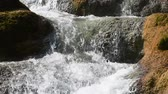 Closeup of water pouring over rough rocks in area of natural waterfalls under bright sunshine, with natural sound Vídeos