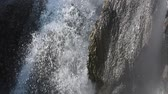 звук : Closeup detail of waterfall and spray over steep rocks mixed with shadows and sunlight, with natural sound