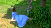 romantismo : Girl in a dress on a swing in the garden.