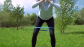 bunda : Young beautiful muscular fitness woman doing squats exercise in the nature. Stock Footage