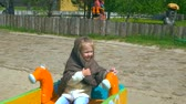 mendil : Little girl in a shawl riding a swing. Stok Video