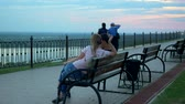 couple in love at sunset sitting on a bench talking, admiring the view