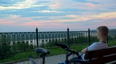 The cyclist guy sat down on a bench to enjoy the sunset. Stock Footage