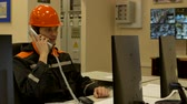 the operator in the helmet sitting in the control room receives calls on the phone controls the production