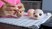 girl knits a crochet bear toy Stock Footage