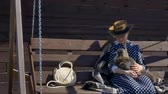 kotki : girl in a hat is resting on a wooden swing in the village with a cat Wideo