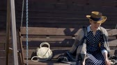 kotki : girl in a hat resting on a wooden swing picks up a cat Wideo