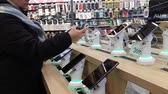 aparelho : Kiev, March 6, 2018, Ukraine. The buyer chooses a smartphone on the counter in one of the electronics supermarkets in Kiev