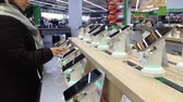 agd : Kiev, March 6, 2018, Ukraine. The buyer chooses a smartphone on the counter in one of the electronics supermarkets in Kiev