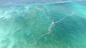 surfe : Windsurfer gliding slowly in calm summer wave of turquoise blue ocean water in Hawaiian seascape in 4k aerial drone view Stock Footage