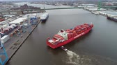 exportação : Big red loaded freight cargo container ship arriving at modern urban industrial river ocean port in 4k aerial drone view Stock Footage