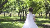 beautiful and delicate bride in white wedding dress with bouquet of flowers on nature in the park