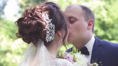 новобрачный : beautiful bride in a white wedding dress is kissing with the groom in a suit outdoors in a park in summer