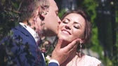 beautiful bride in a white wedding dress is kissing with the groom in a suit outdoors in a park in summer