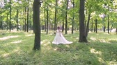 koronka : beautiful and delicate bride in white wedding dress with bouquet of flowers on nature in the park