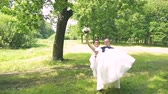 the groom in a suit is carrying a beautiful happy bride in her arms in the park in summer on a nature background