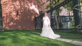beautiful bride in a white summer dress on a brick wall background