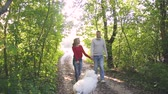 young couple walking in the summer forest with a white dog
