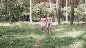 young couple in love walks in the summer park among the pines
