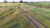 ucraniano : Aerial footage of female riding bike. Countryside road. Agricultural field in summer. Ukrainian nature Archivo de Video
