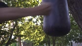 обученный : Boxer punching bag, on the outdoor. Slow motion sequence.
