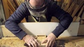 furniture : the man works at the machine with wood