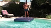 Funny Jump In The Pool. Video of funny man jumping on water mat in the swimming pool.