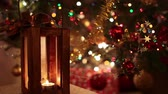 winter : Video clip of Christmas lantern with magical lights of Christmas tree in the background.