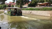 vezetett : LJUBLJANA, SLOVENIA - AUGUST 29, 2018: The Barjanka tourist boat on Ljubjanica river under the Butchers bridge. Barjanka offers guided tours and can take up to 36 people.