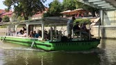 vezetett : LJUBLJANA, SLOVENIA - AUGUST 29, 2018: The Green Dragon tourist boat on Ljubjanica river under the Butchers bridge. The Green Dragon offers guided river tours. Stock mozgókép
