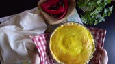 recheado : Woman brings to the table a freshly baked pie and puts it on a wooden cutting board.