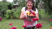 Happy elderly woman in her garden showing a bowl with fresh fruit and vegetables freshly picked. Стоковые видеозаписи