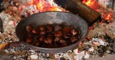 Chestnuts roasting in an old pan inside the fireplace - Concept of winter holidays in front of the chimney
