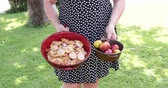 Caucasian woman outdoor in the garden carrying in one hand a bowl with plums and in the other hand a terracotta baking tray with slices of fruit and sugar for a cake preparation.