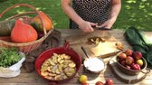 Woman cutting plums in pieces on a table outside iin the garden - Autumn cooking outdoors time lapse technique.
