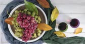Plate with pink and white table grapes decorated with autumn leaves rotating on a white wooden table and two glasses of red wine - Concept of autumnal harvest - Table top view with copy space Archivo de Video