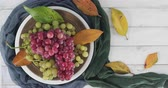 Plate with pink and white table grapes decorated with autumn leaves rotating on a white wooden table - Table top view with copy space Стоковые видеозаписи