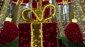 Huge Christmas tree of  lights and golden garlands, with big red balls and presents Archivo de Video