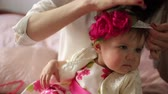 dressing : women dressing her baby girl for birthday party Stock Footage