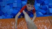 assise : DNIPRO, UKRAINE-April 27, 2018: Children funny games in foam rubber pit in trampoline center, April 27, 2018 in Dnipro, Ukraine