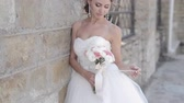 momento : beautiful bride standing at the wall
