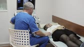 baba : Male doctor talking with young woman patient in ultrasound diagnostic room.