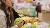 refrigerated : Young woman in shopping selecting fresh bananas at grocery store