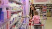 refrigerated : Woman with daughter picking fresh dairy products in refrigerated section