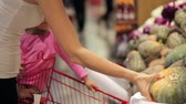 squash family : Young mother with little daughter in trolley selecting a pumpkin at supermarket Stock Footage