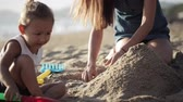мама : Young mother with little doughter playing with sand on the beach